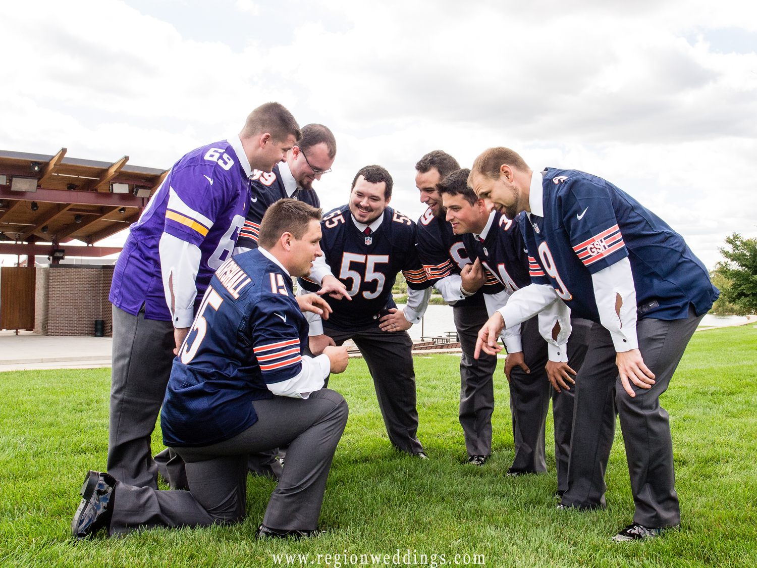 The groom instructs his groomsmen in a football huddle.