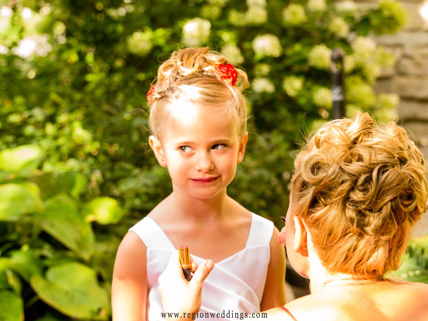 Mom helps her daughter, the flower girl with some last minute touch ups of her lipstick.