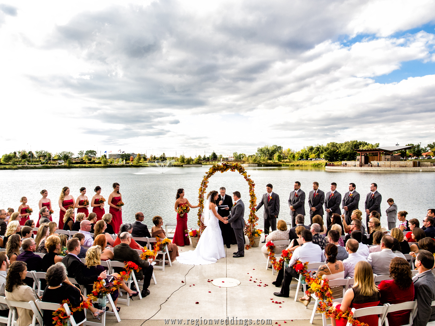Friends and family look on as the arch is decorated in Fall colors at an outdoor wedding at Centennial Park.