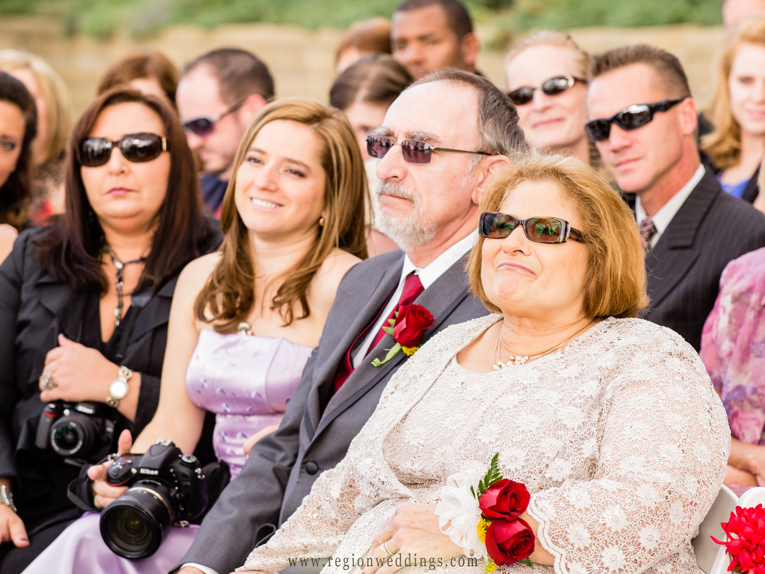 Family of the groom watch as their son and brother gets married in a Fall wedding ceremony.