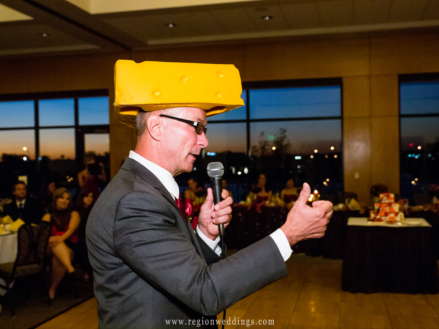 The father of the bride wears a Green Bay Packers cheesehead hat while toasting the ride and groom at their wedding reception.