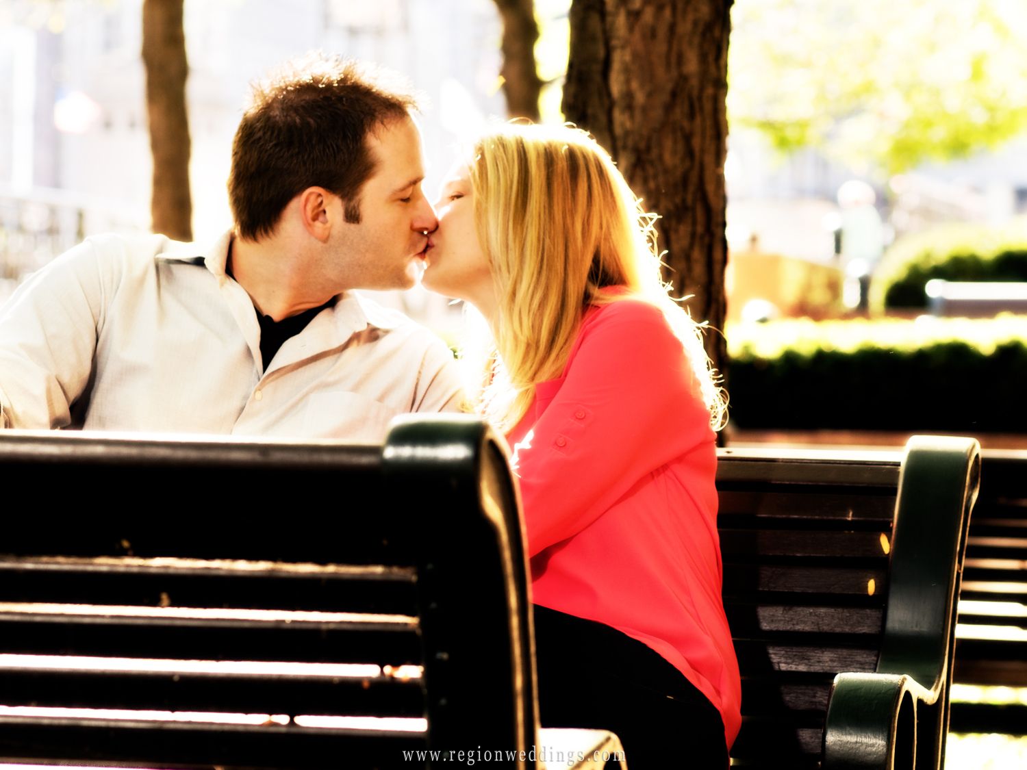 A couple in love share a romantic kiss on a park bench in Chicago during their engagement photo session.