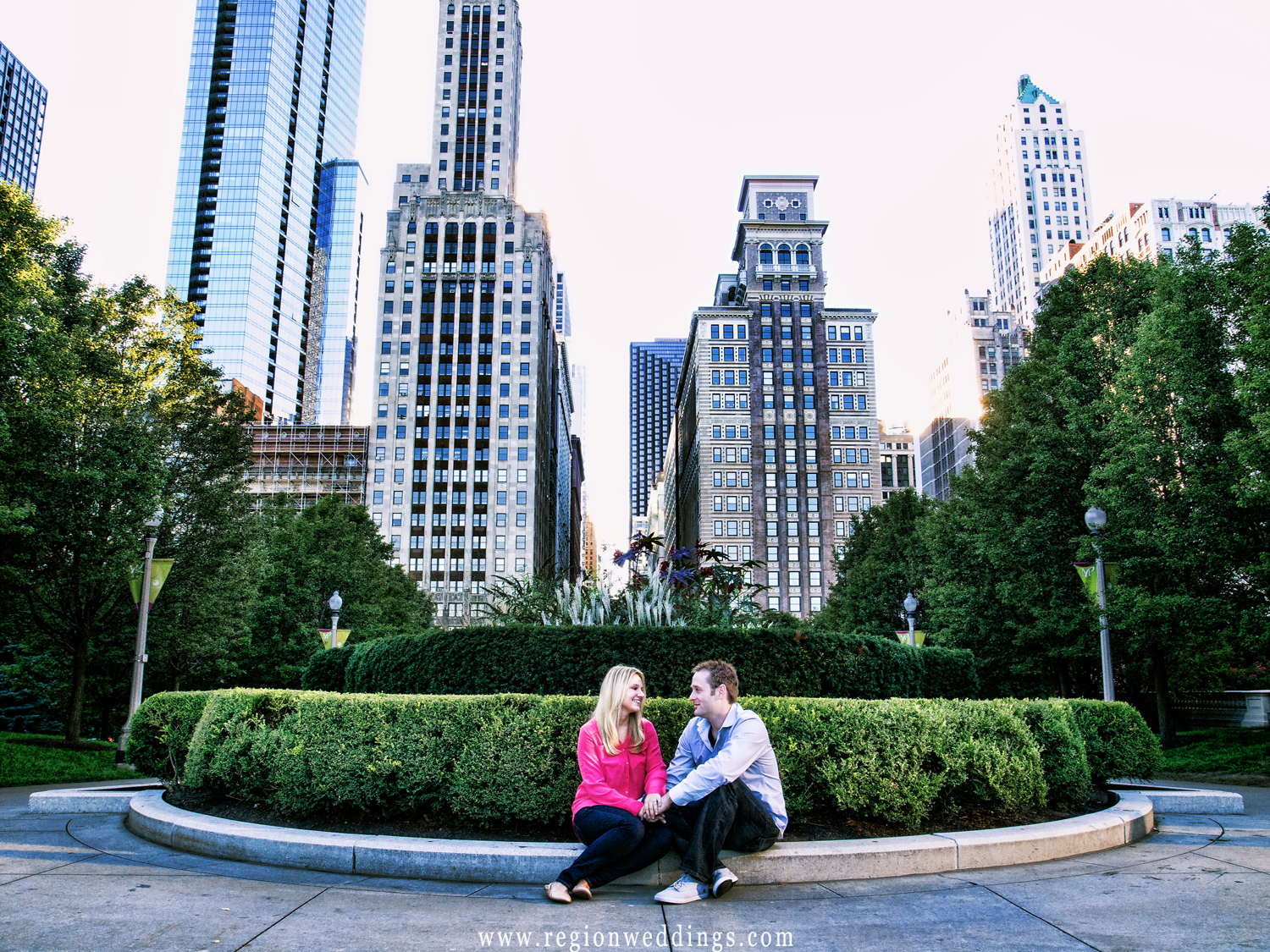 A couple sits at the edge of a flower garden with the tall buildings of Chicago in the background.