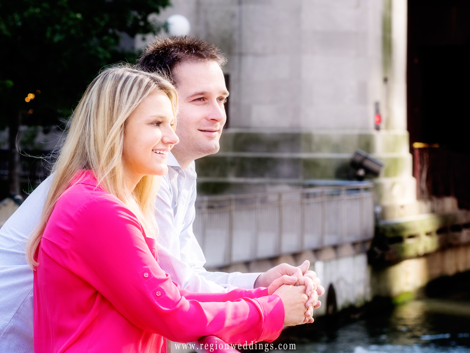 An engaged couple overlooks the Chicago River during their engagement session.