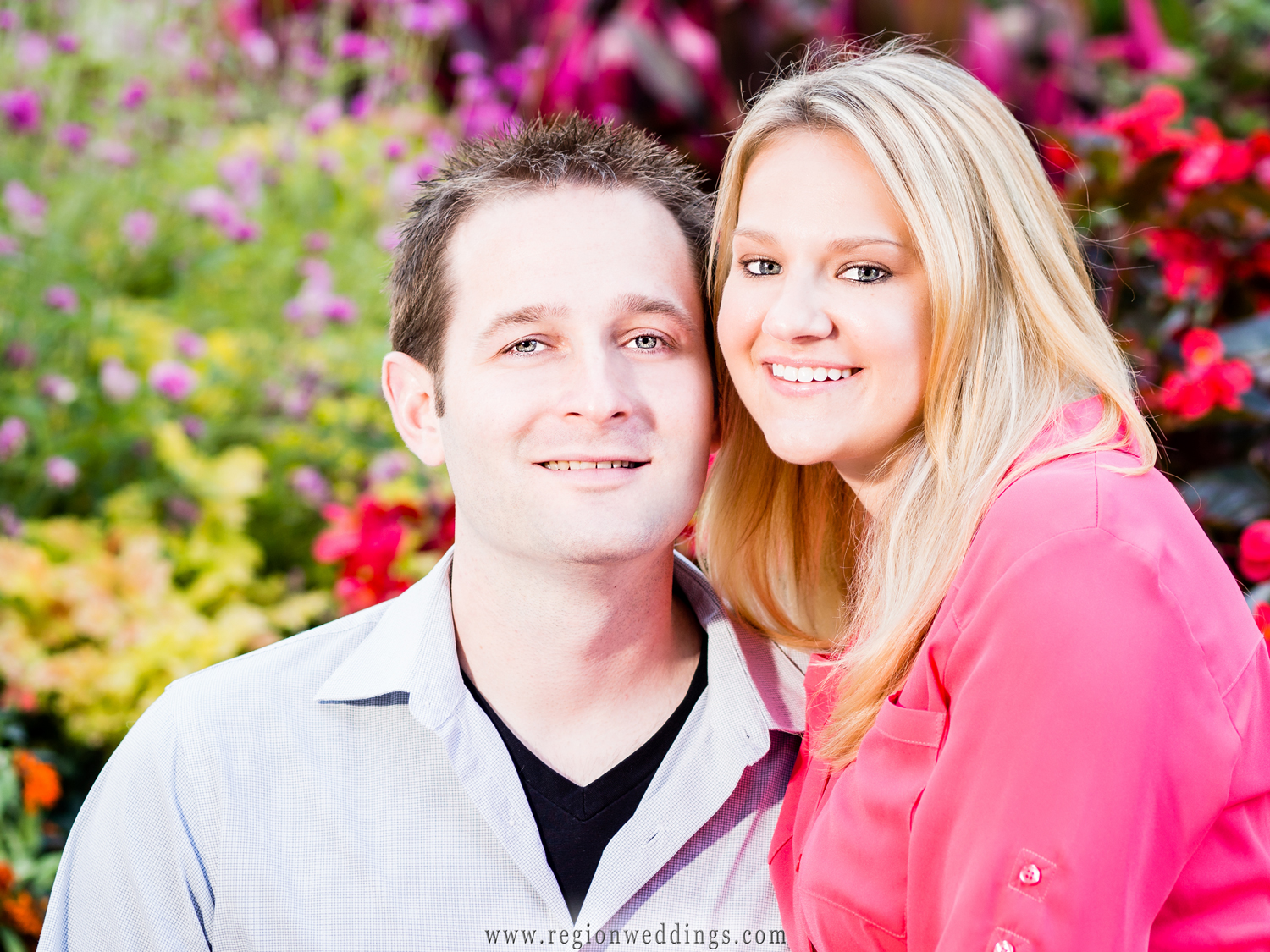 A loving smiles at the camera with beautiful red and pink flowers in the background.
