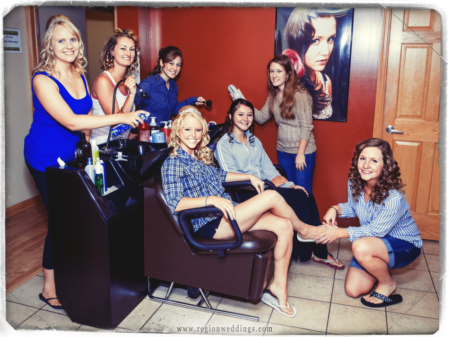 The bride and her bridesmaids gather around the washing station at Studio 4 hair salon in this fun, retro styled wedding photo.