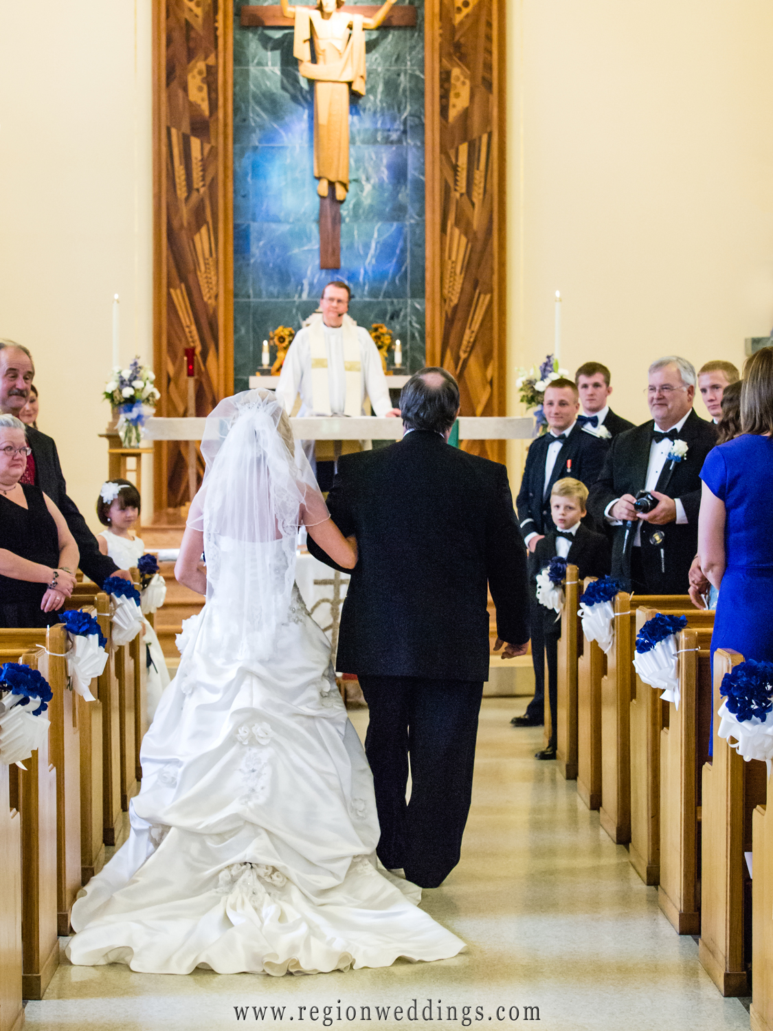 The bride's father walks her down the aisle at St. Mary Church in Griffith.