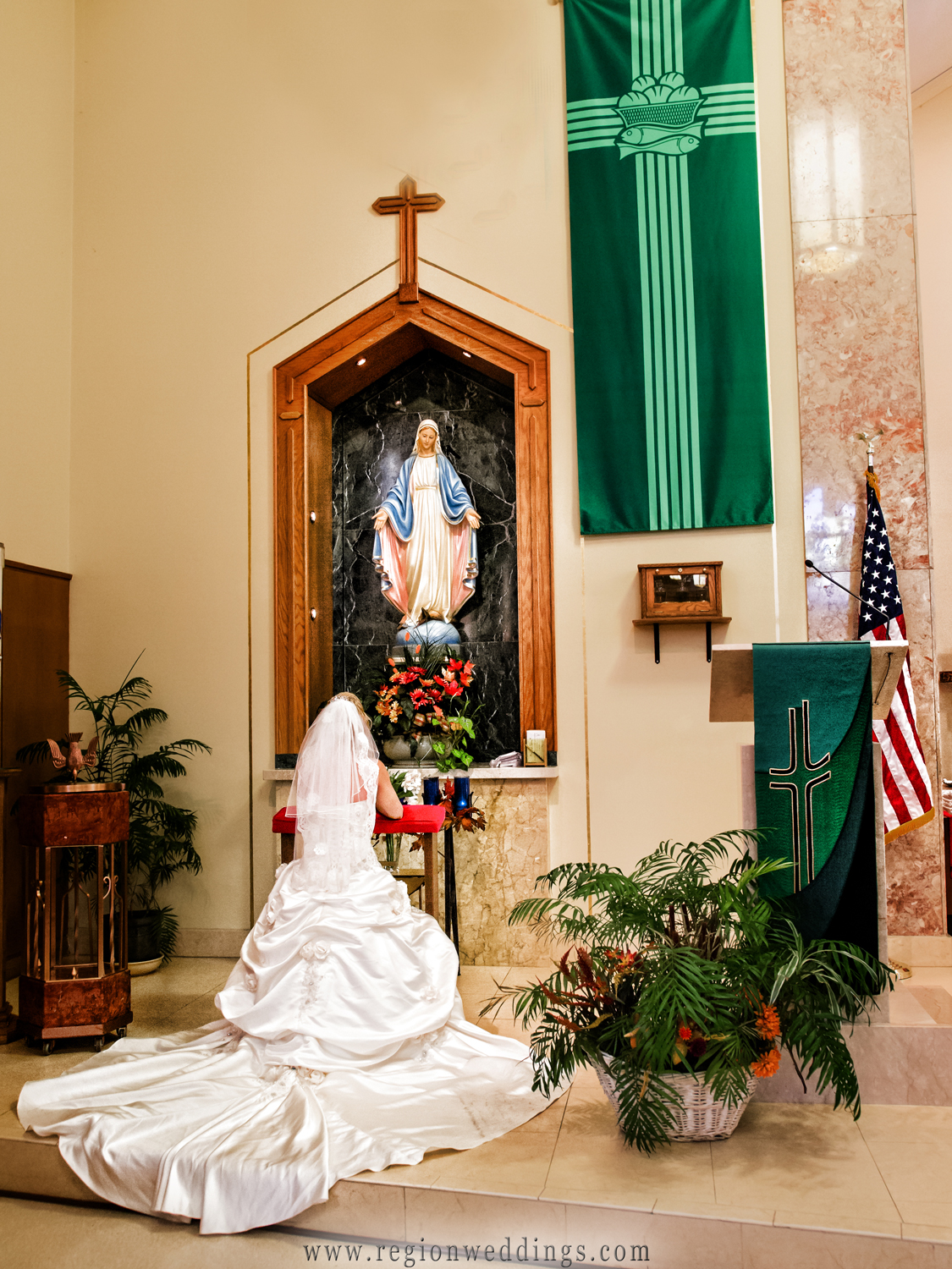 The bride prays at the statue of Mother Mary.