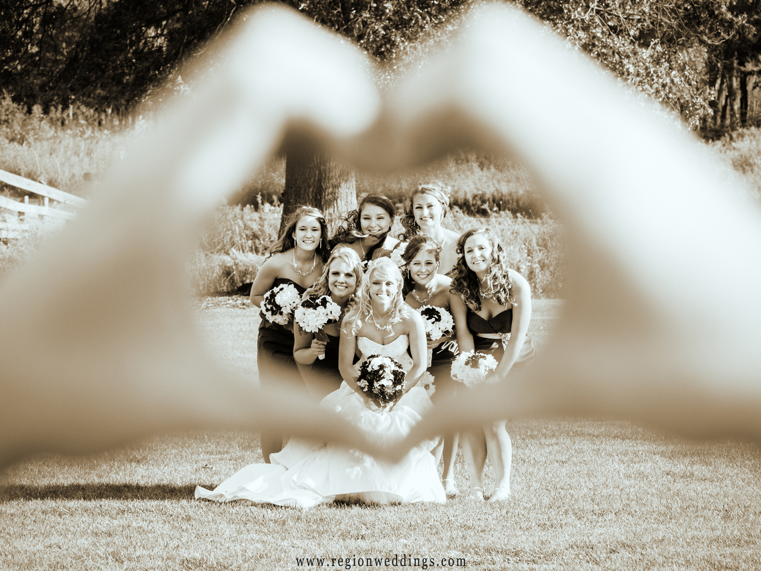 The bridesmaids huddle up together within a heart.