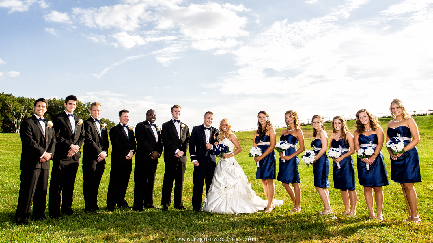 The wedding party poses in front of the large sled hill at Oak Ridge Prairie County Park in Indiana.