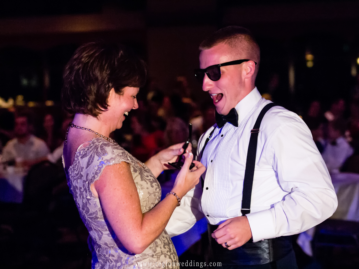 A candid wedding photo of the groom and his mom wear sunglasses as they dance together at his wedding reception.