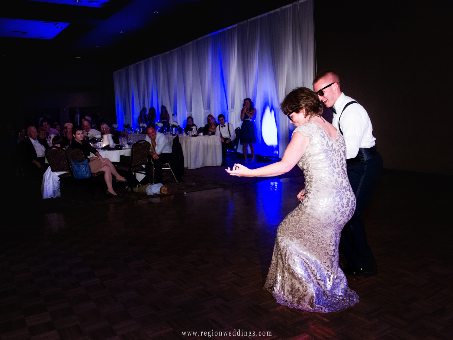 The groom and his mom play air guitar on the dance floor during his wedding reception.