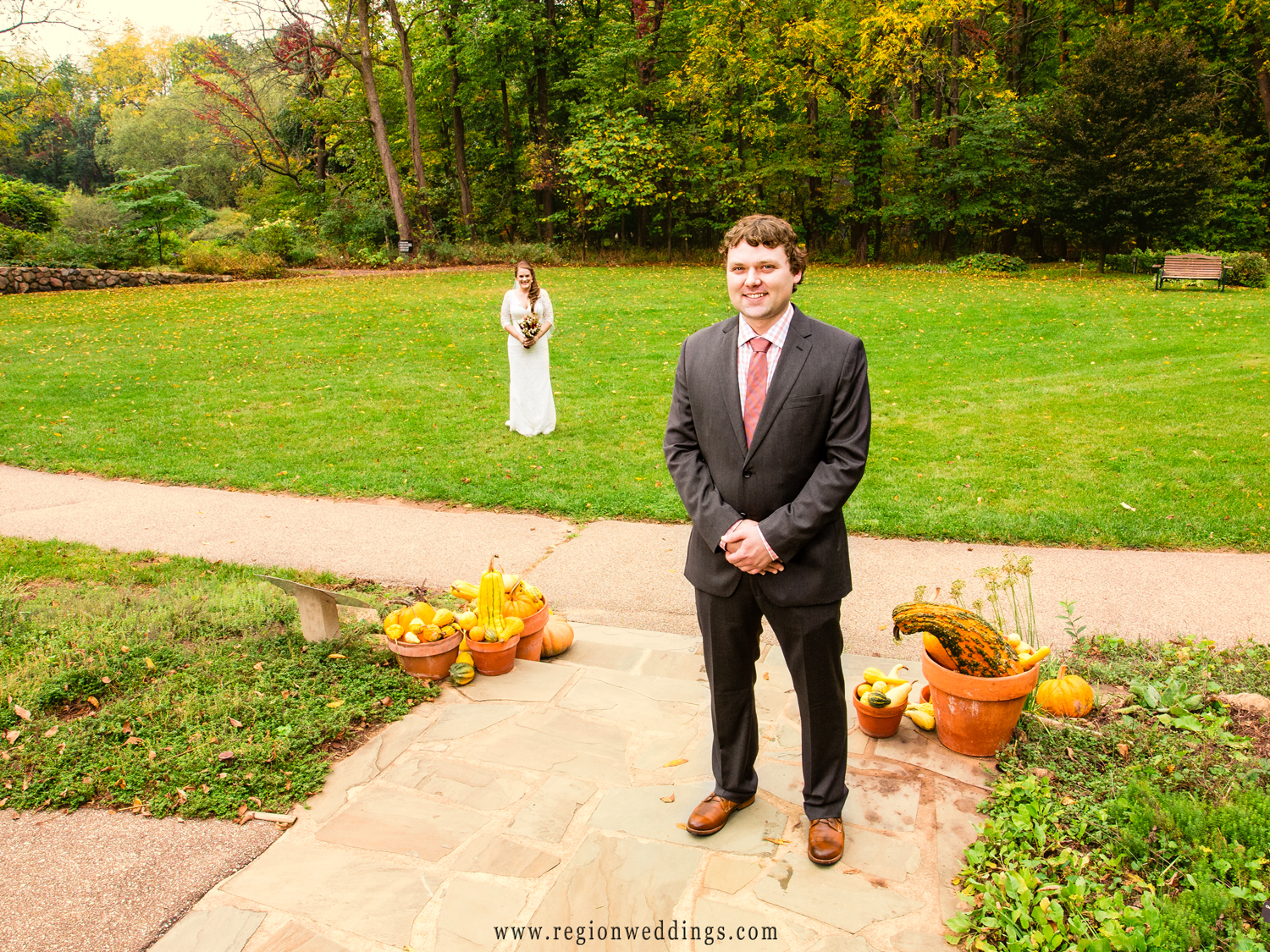 The bride walks toward her soon to be husband in a beautiful green field surrounded by trees and Autumn leaves.