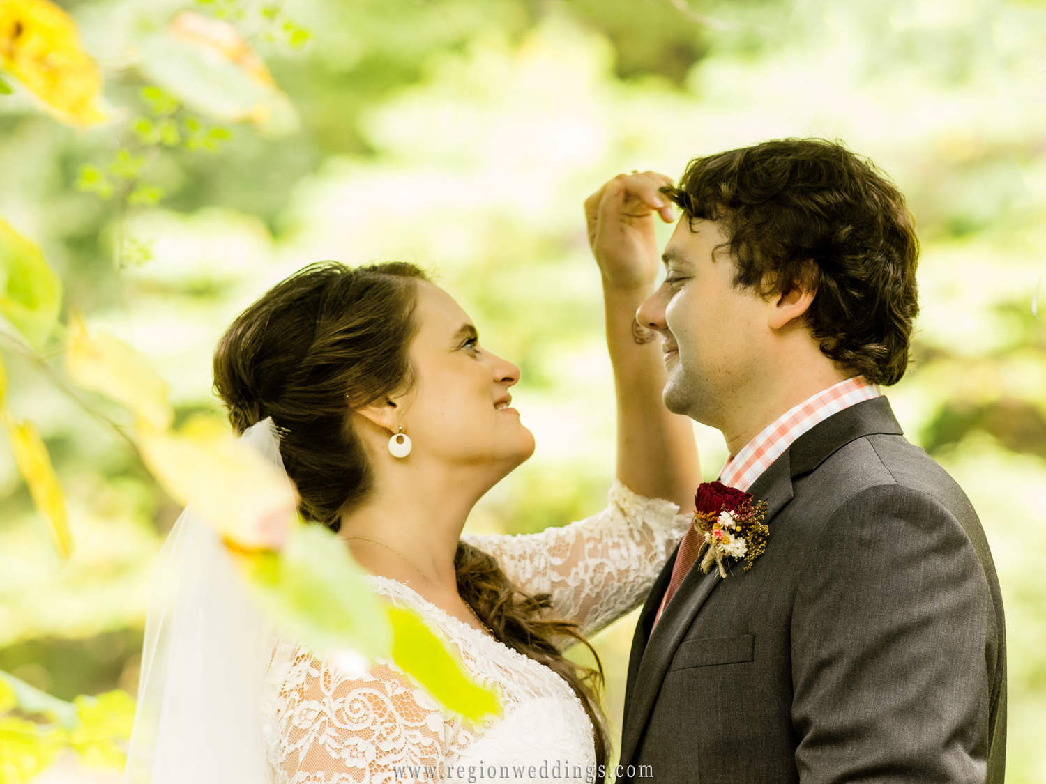 A candid photo of the bride brushing the grooms hair surrounded by wonderful greenery.