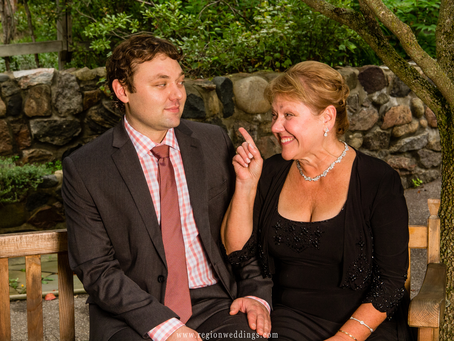 The groom's mother gives some last minute advice to her son just before the wedding ceremony.