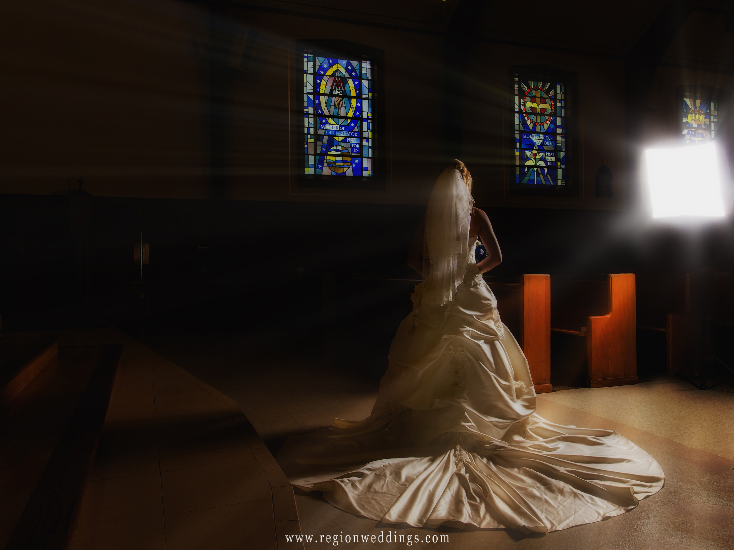 A dramatic looking image of the back of the bride's dress inside a dark church.