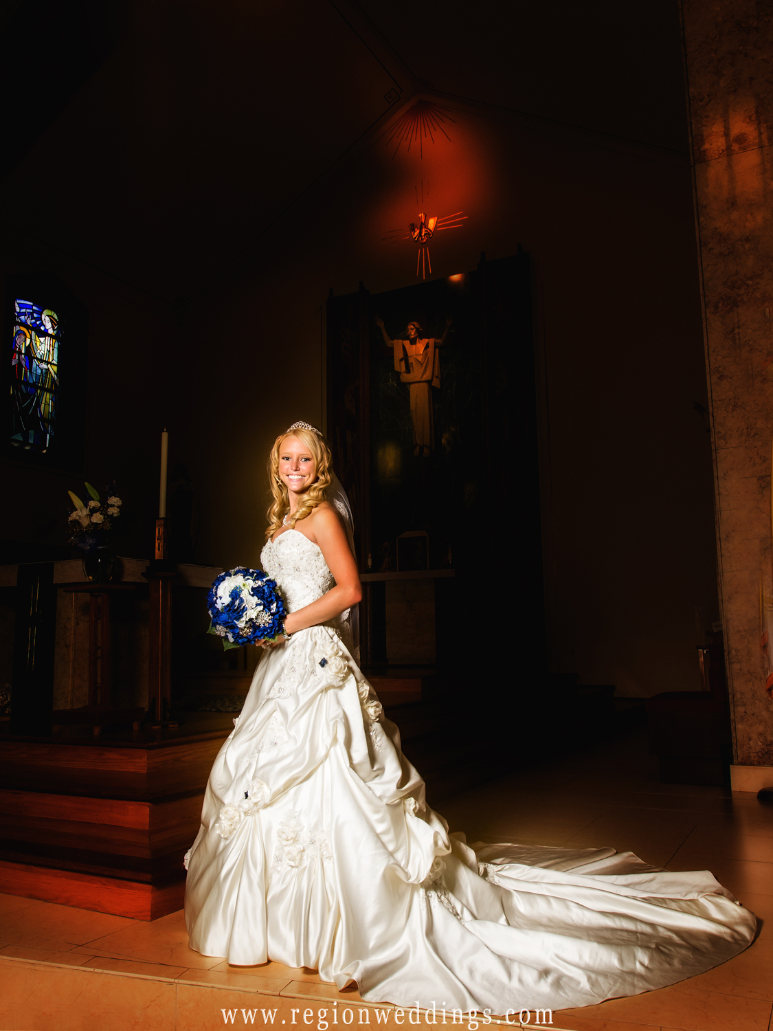 The bride clutches her blue bouquet of flowers while posing for a wedding photo inside of St. Mary's Church in Griffith.