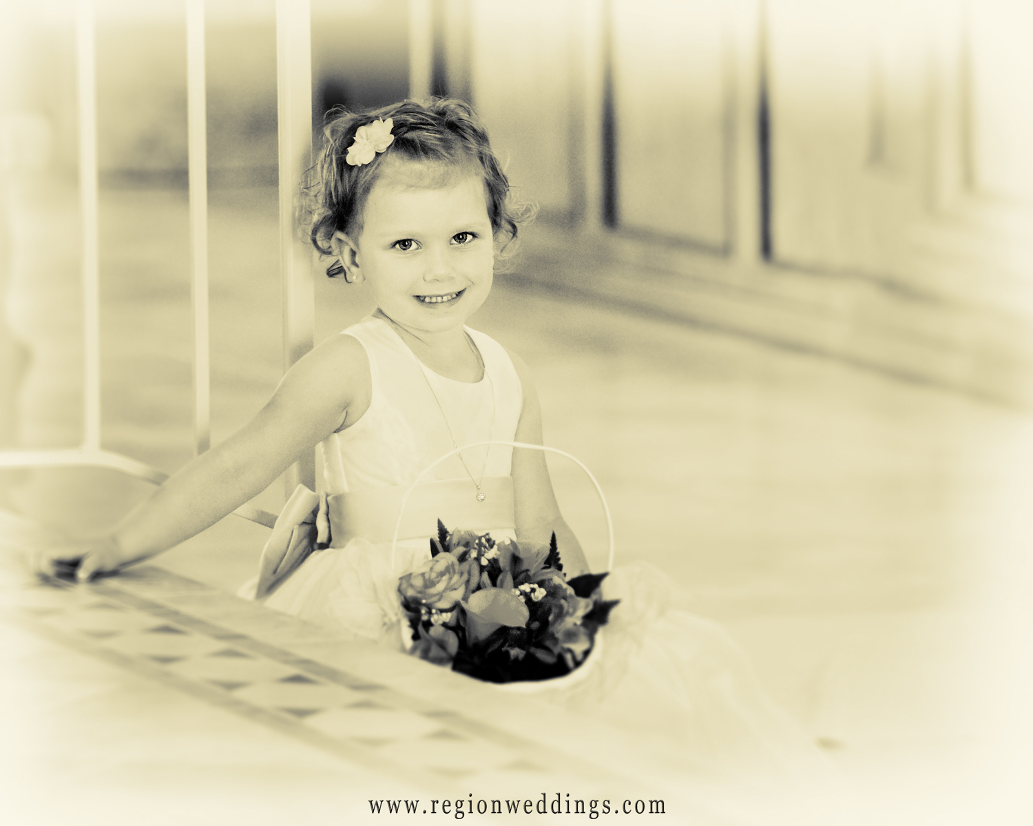 The flower girl takes a break during a Catholic wedding ceremony.