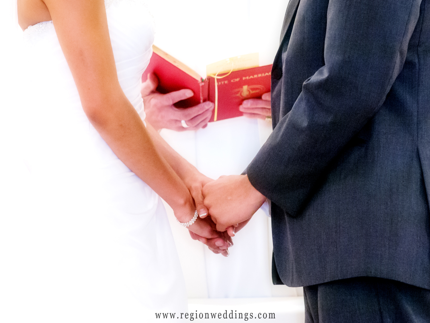 The bride and groom clasp their hands together while the priest reads from a red bible during their church wedding ceremony.