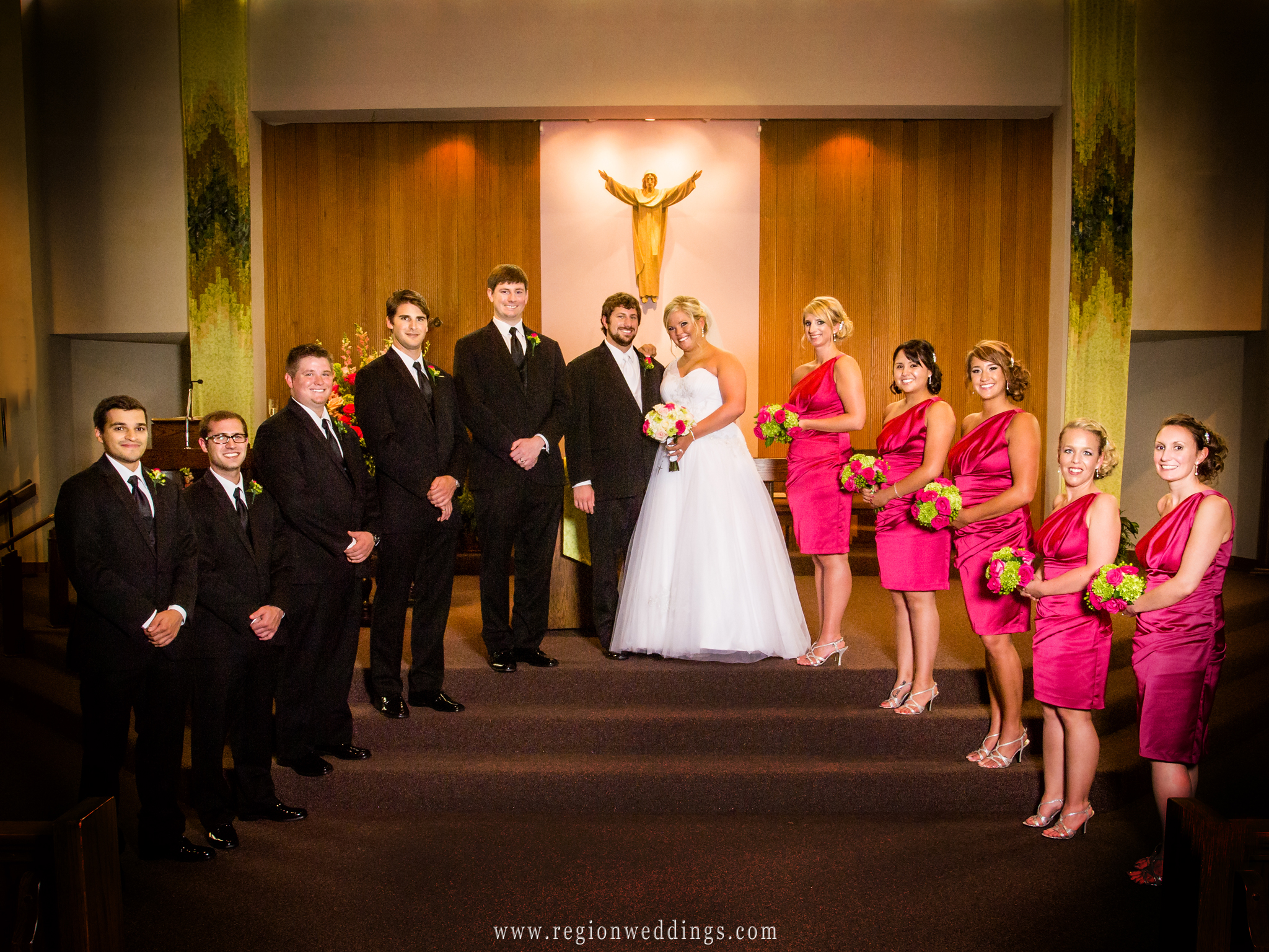 The wedding party group photo at the altar inside of a church in Valparaiso.