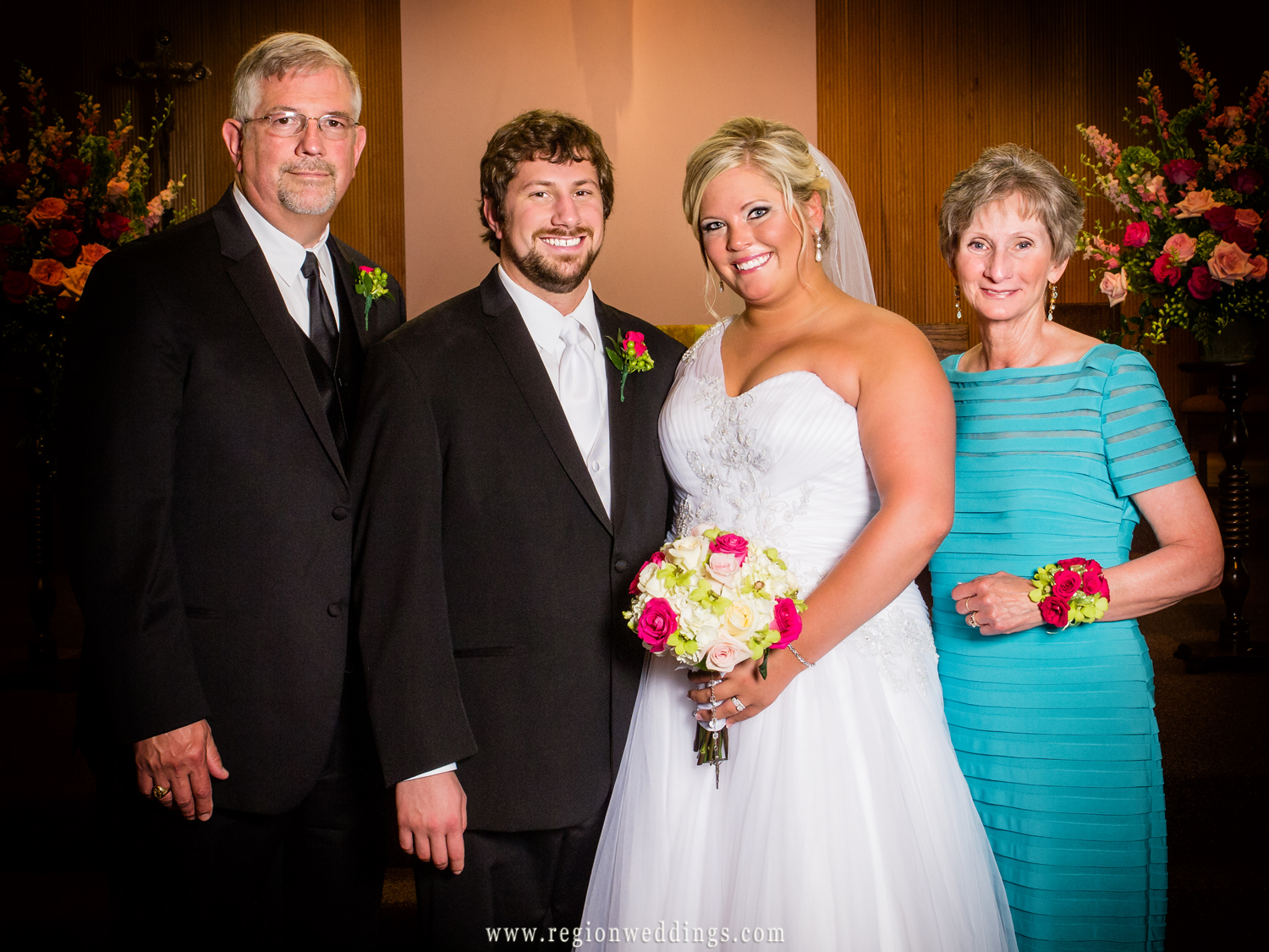 Parents of the groom pose with him and his bride at the altar of St. Elizabeth Ann Seton Church in Valparaiso, Indiana.