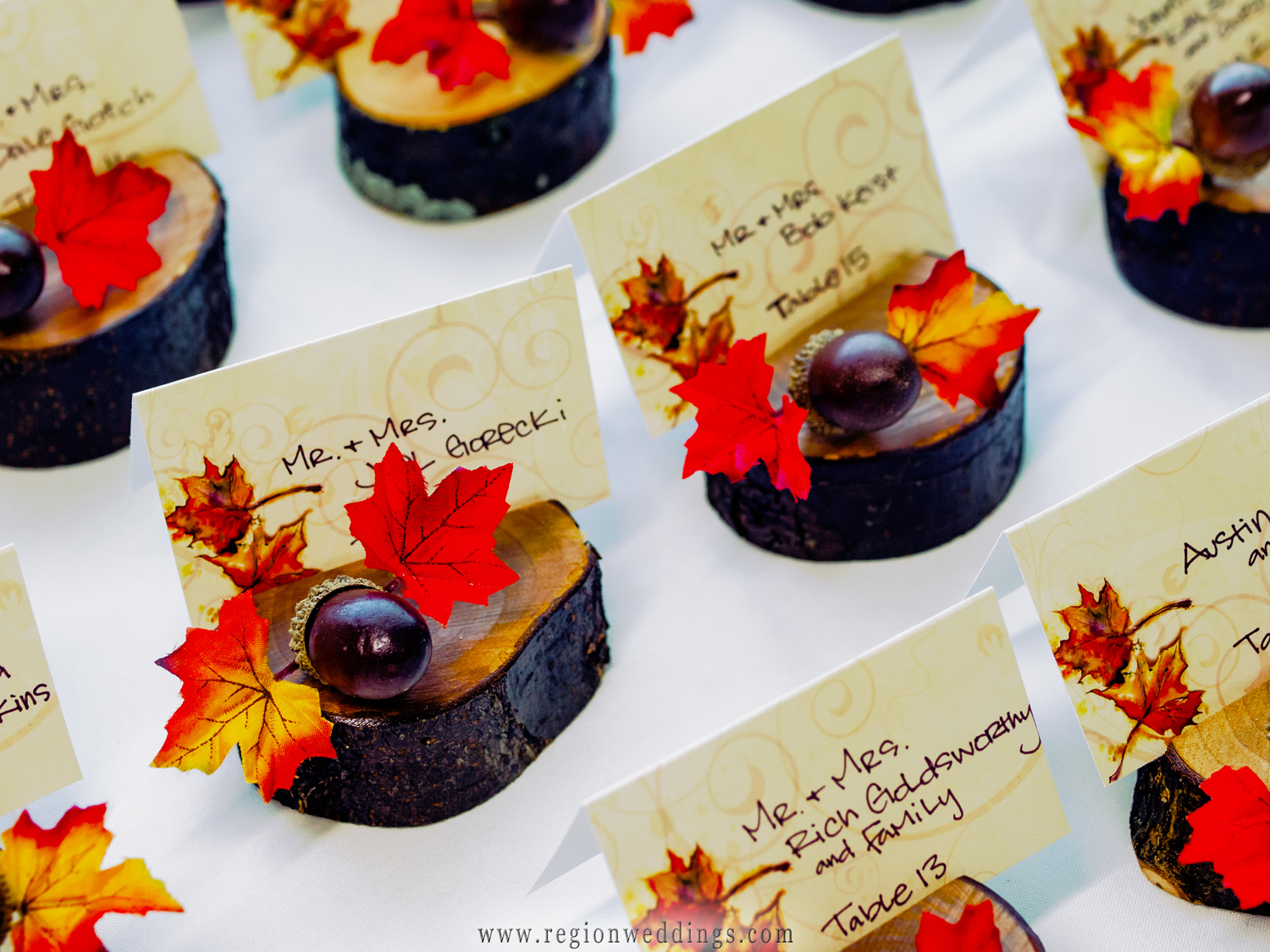 Fall wedding table cards made of miniature logs with the seating card inside the carved out slit.