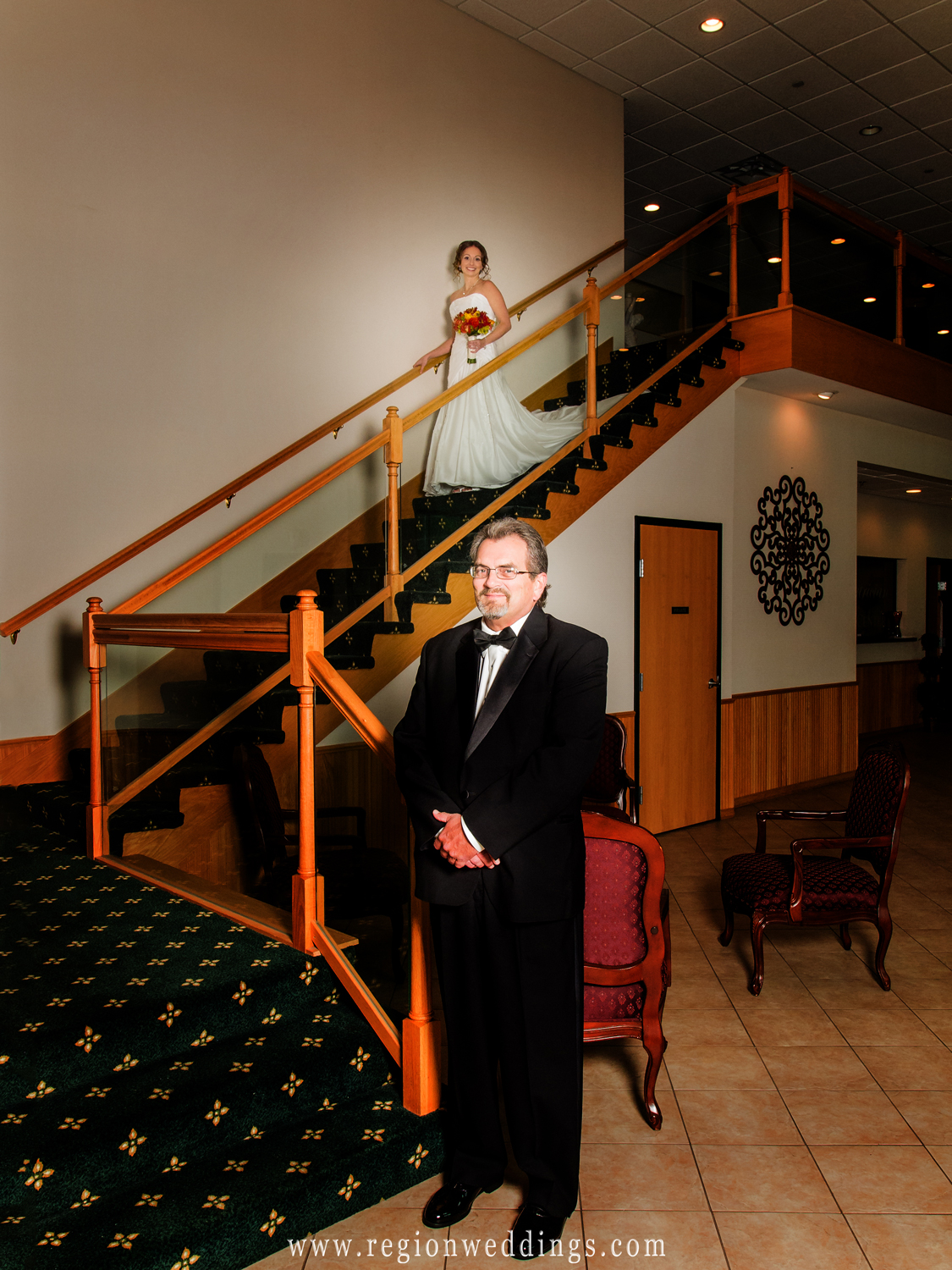 A father awaits his daughter, the bride, for his first look at the bottom of the staircase at The Patrician banquet hall.