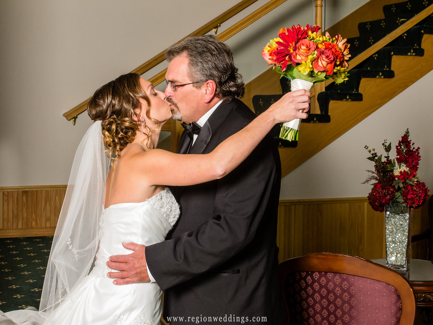 A bride kisses her Dad after he sees her in her wedding dress for the first time.