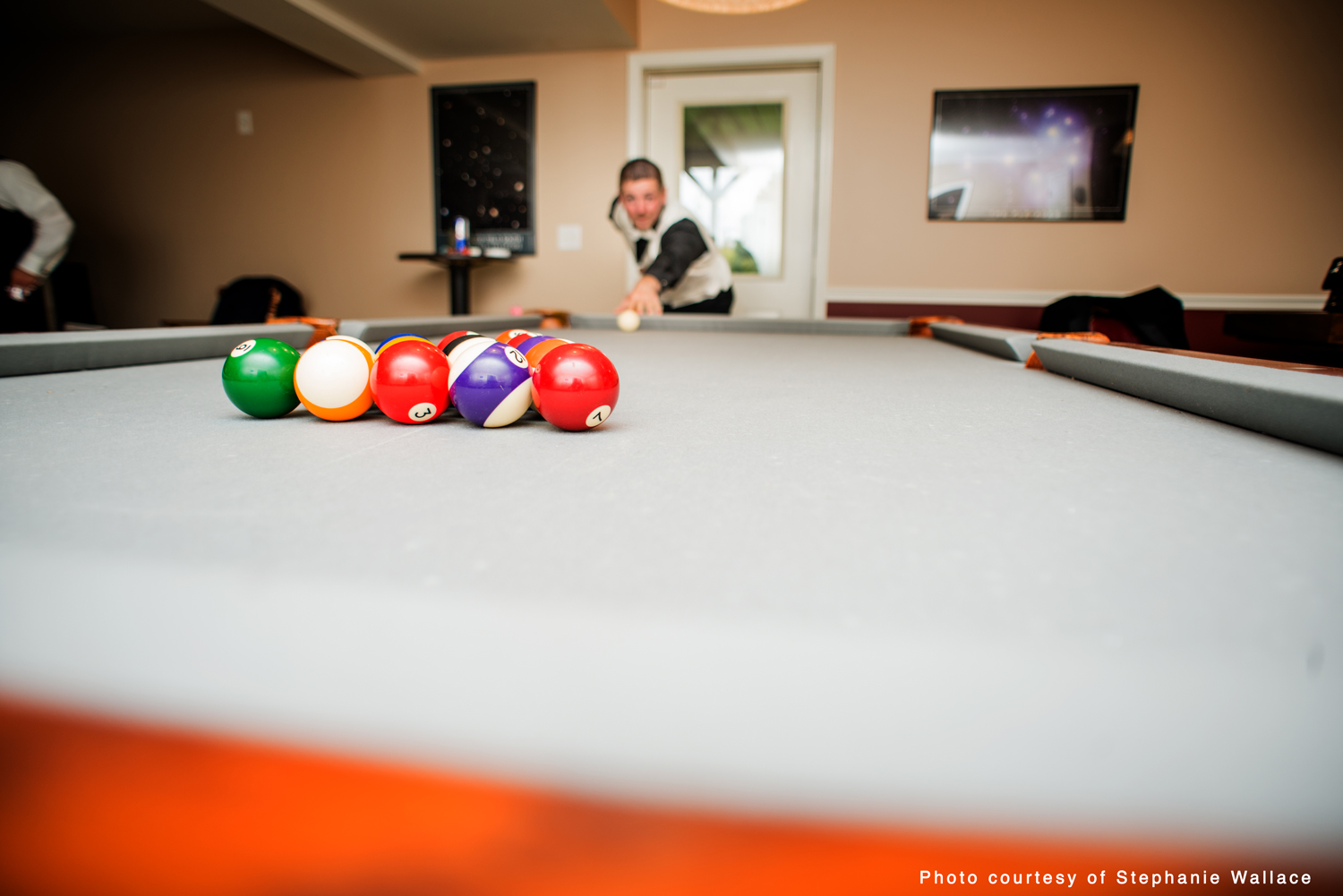 The groom shoots pool to shake the nerves on the morning of his wedding.