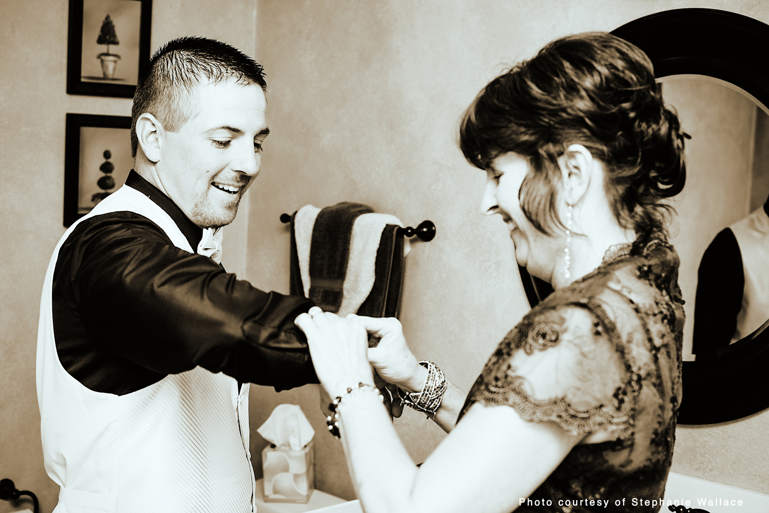 The groom's mother helps him with the cufflinks on his suit.