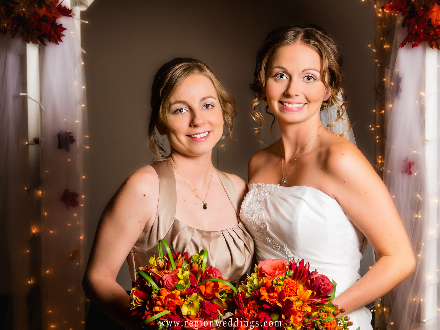 The bride's sister and maid of honor poses for a portrait surrounded by autumn decorations at The Patrician.