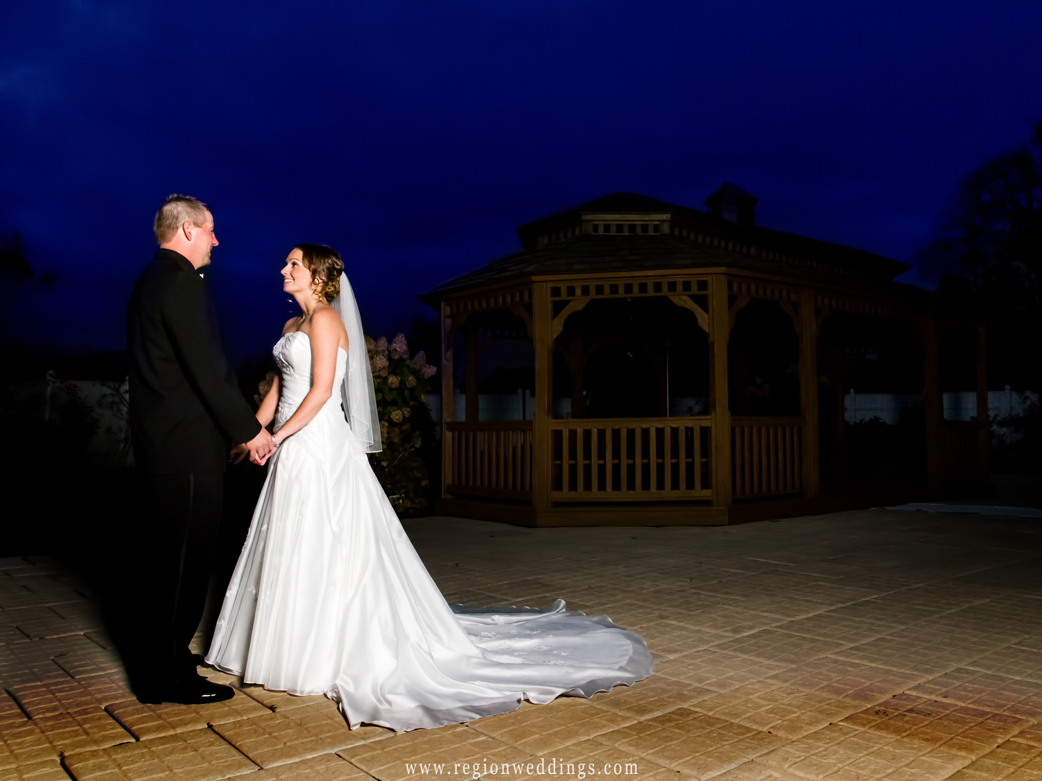 The bride and groom stand outside the gazebo at The Patrician in Schererville, Indiana during the twilight hour.