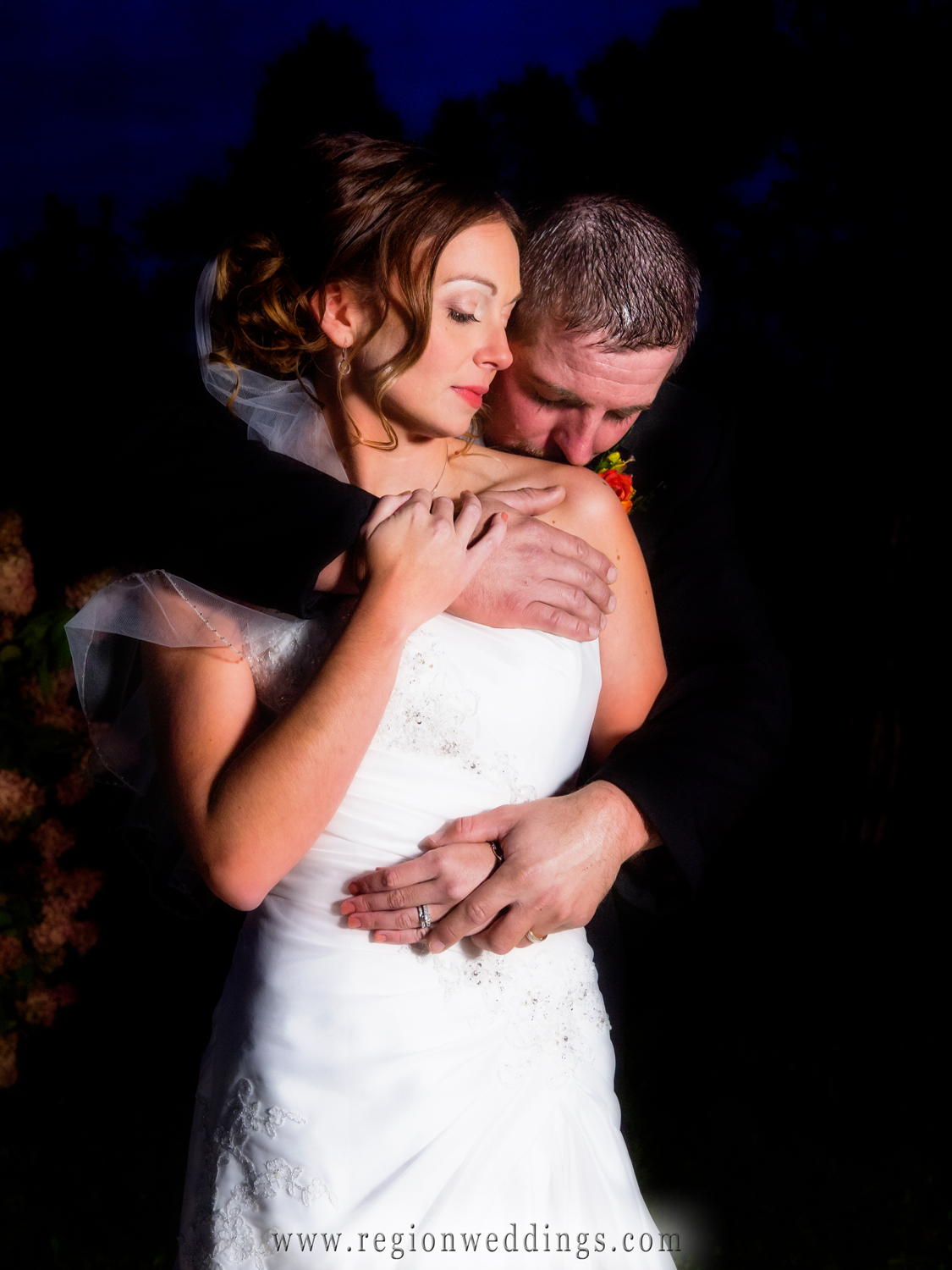 The bride and groom embrace as night fall.