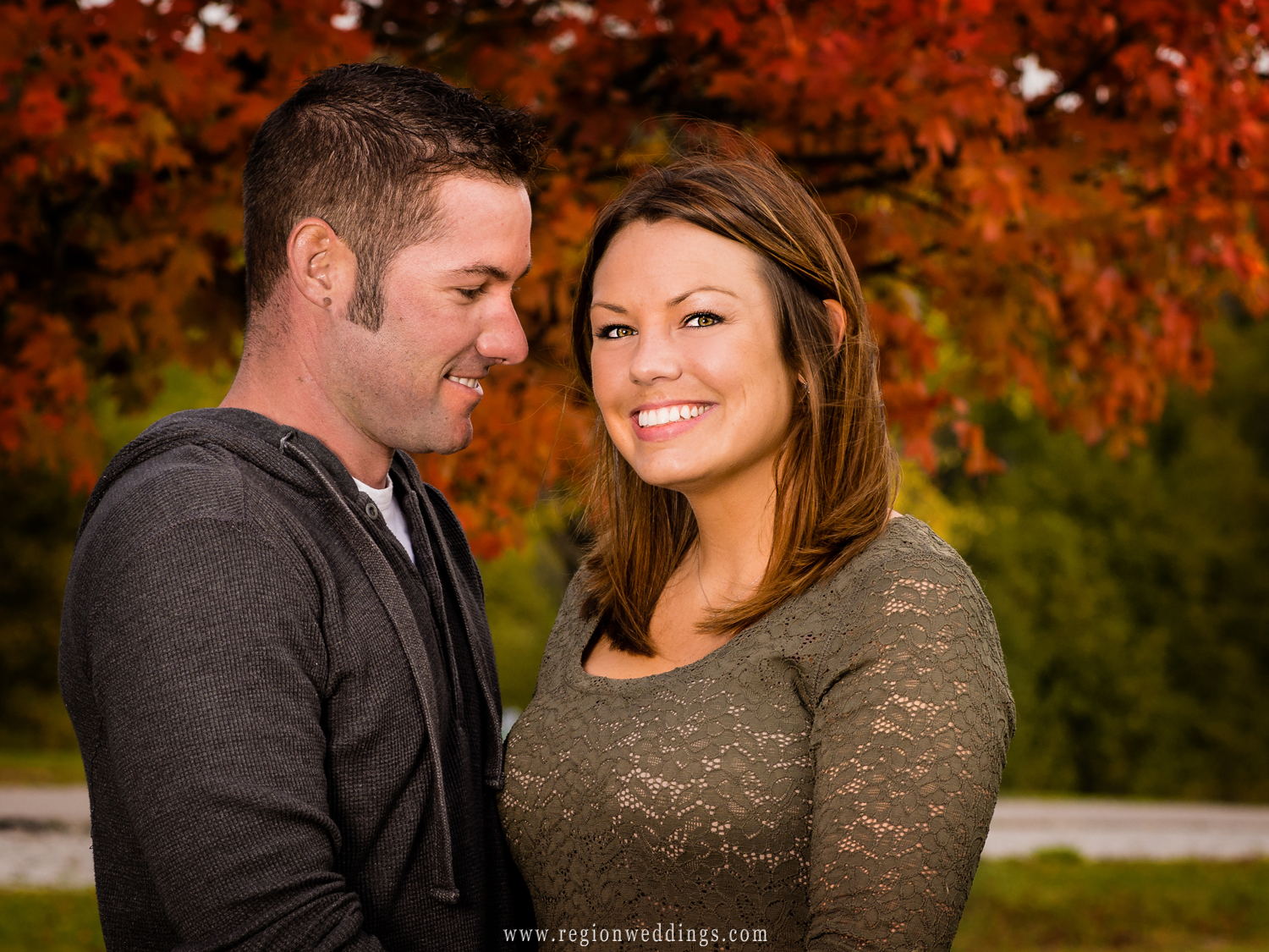 A man smiles toward his fiancé for their Fall engagement photo with a tree with bright orange leaves in the background.