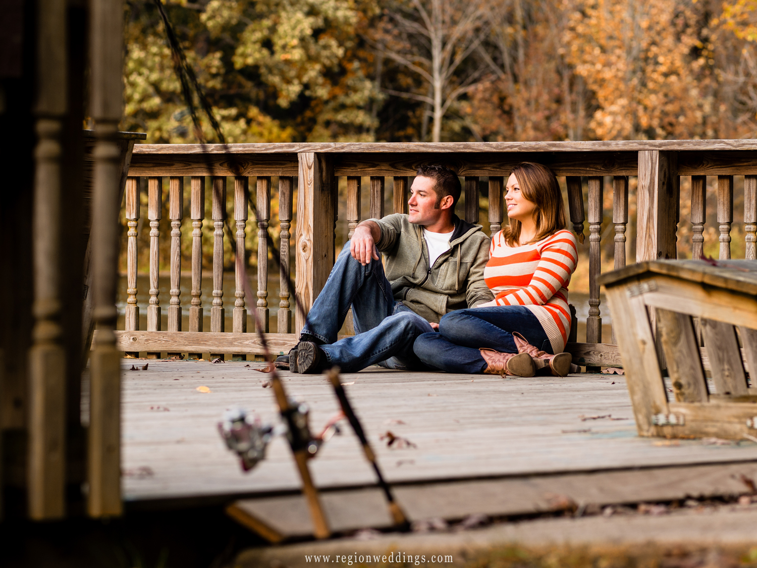 A couple relaxes on a lake pier with their fishing poles in the foreground.