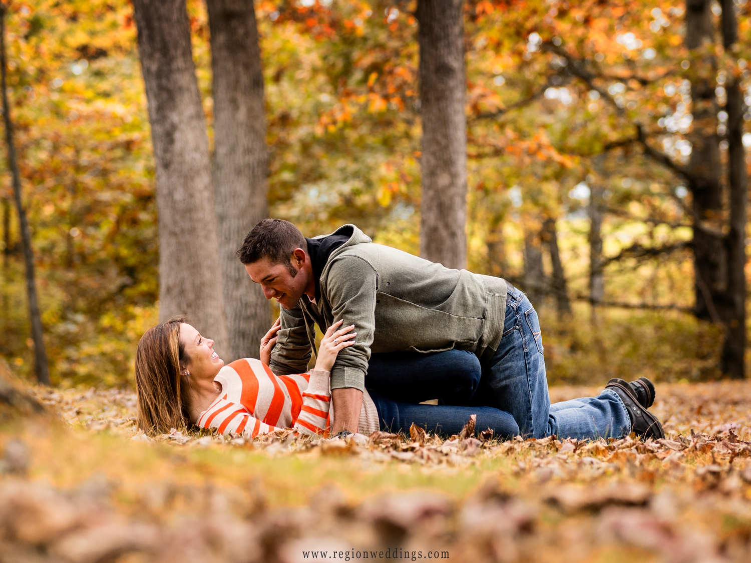 A couple playfully rolls around in a pile of leaves during a romantic walk in the park.