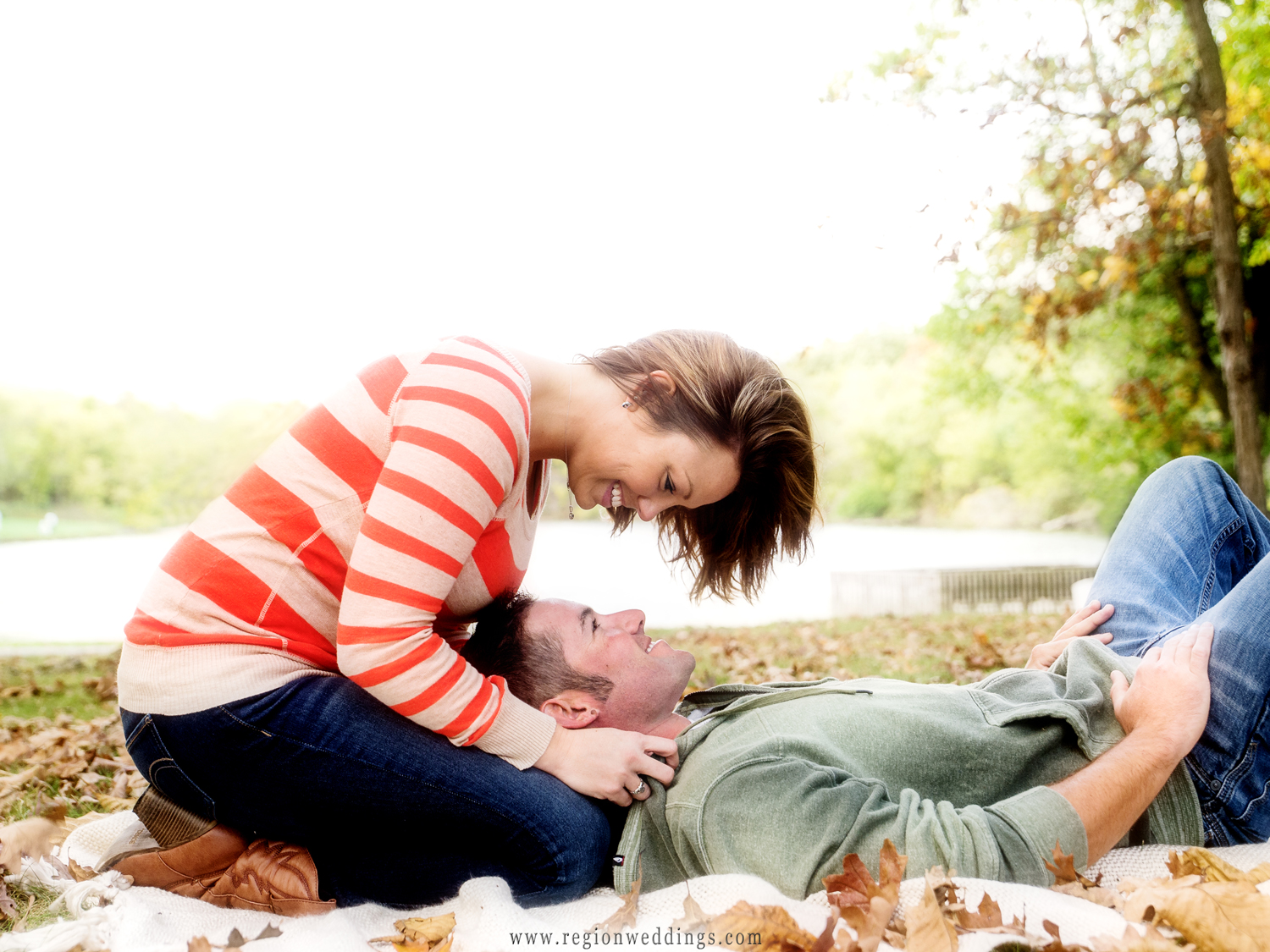 A romantic engagement photo of a couple laying on a blanket at Lemon Lake Park with Fall leaves all around them.