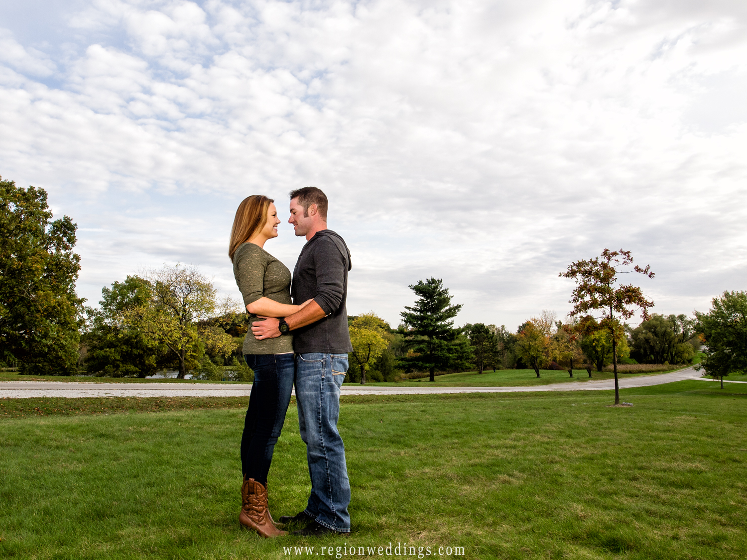 A couple embraces between trees and underneath the open sky for an Autumn engagement photo.