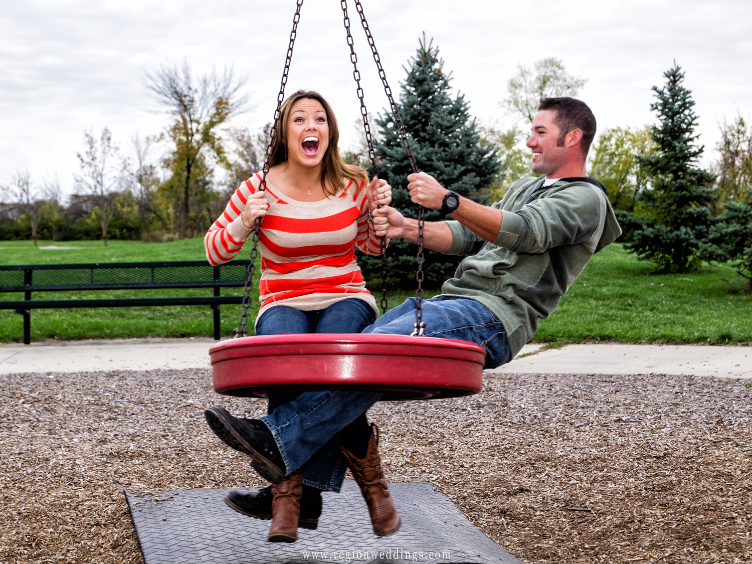 A couple plays on a swing set at the playground of a local park.