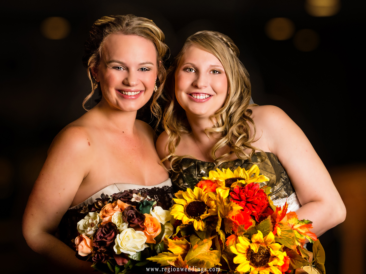 A bride and her bridesmaid shows off their Fall flowers in a portrait.