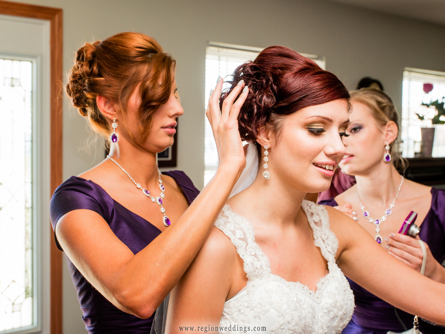 the bridesmaids help secure the bride's veil before her wedding ceremony in Calumet City, Illinois.
