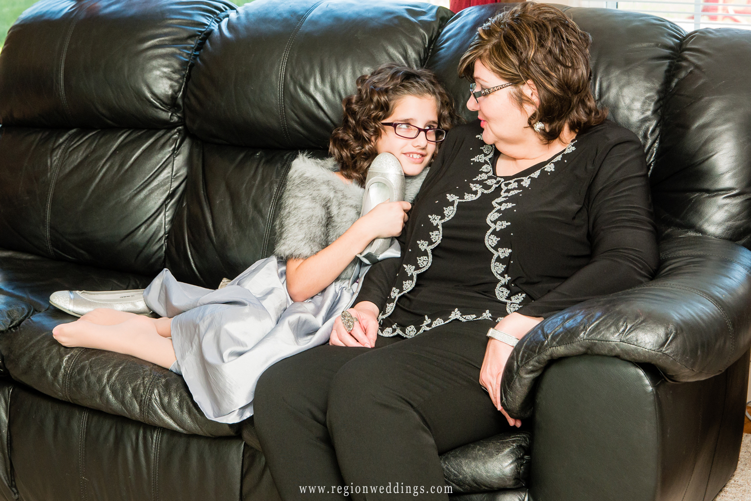 The flower girl curls up on the sofa on the morning of her big sister's wedding.