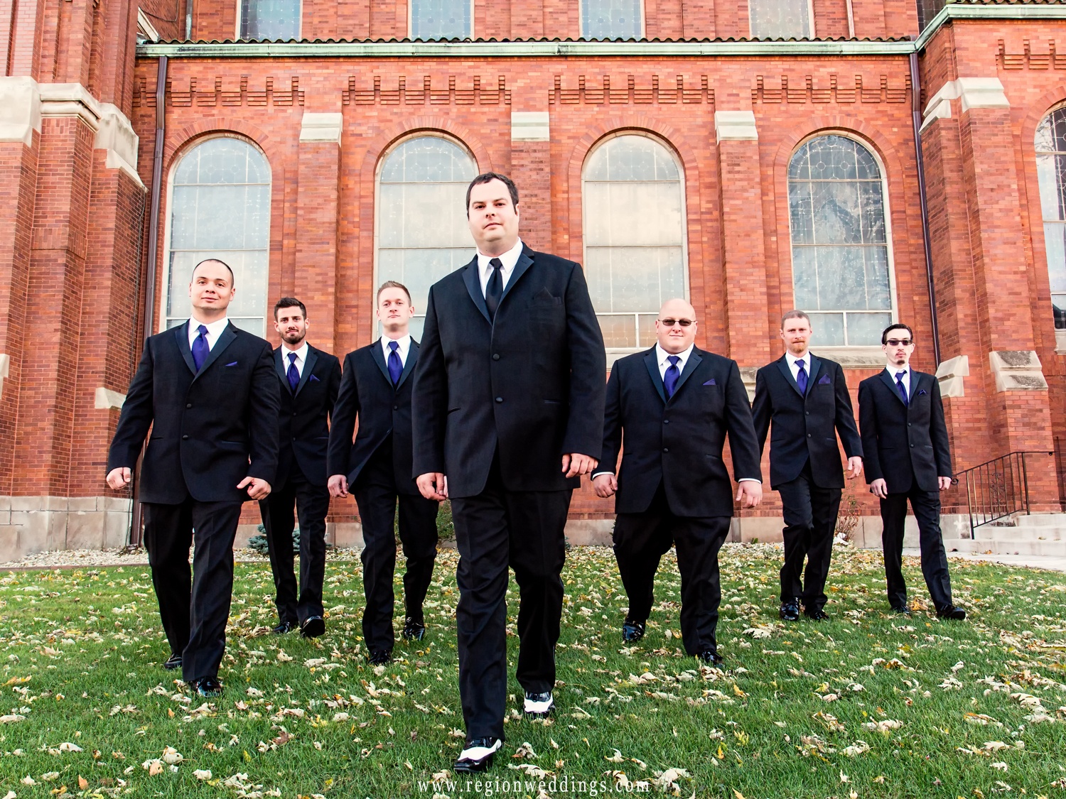The groomsmen take a walk in the autumn leaves outside Saint Andrew's Church.
