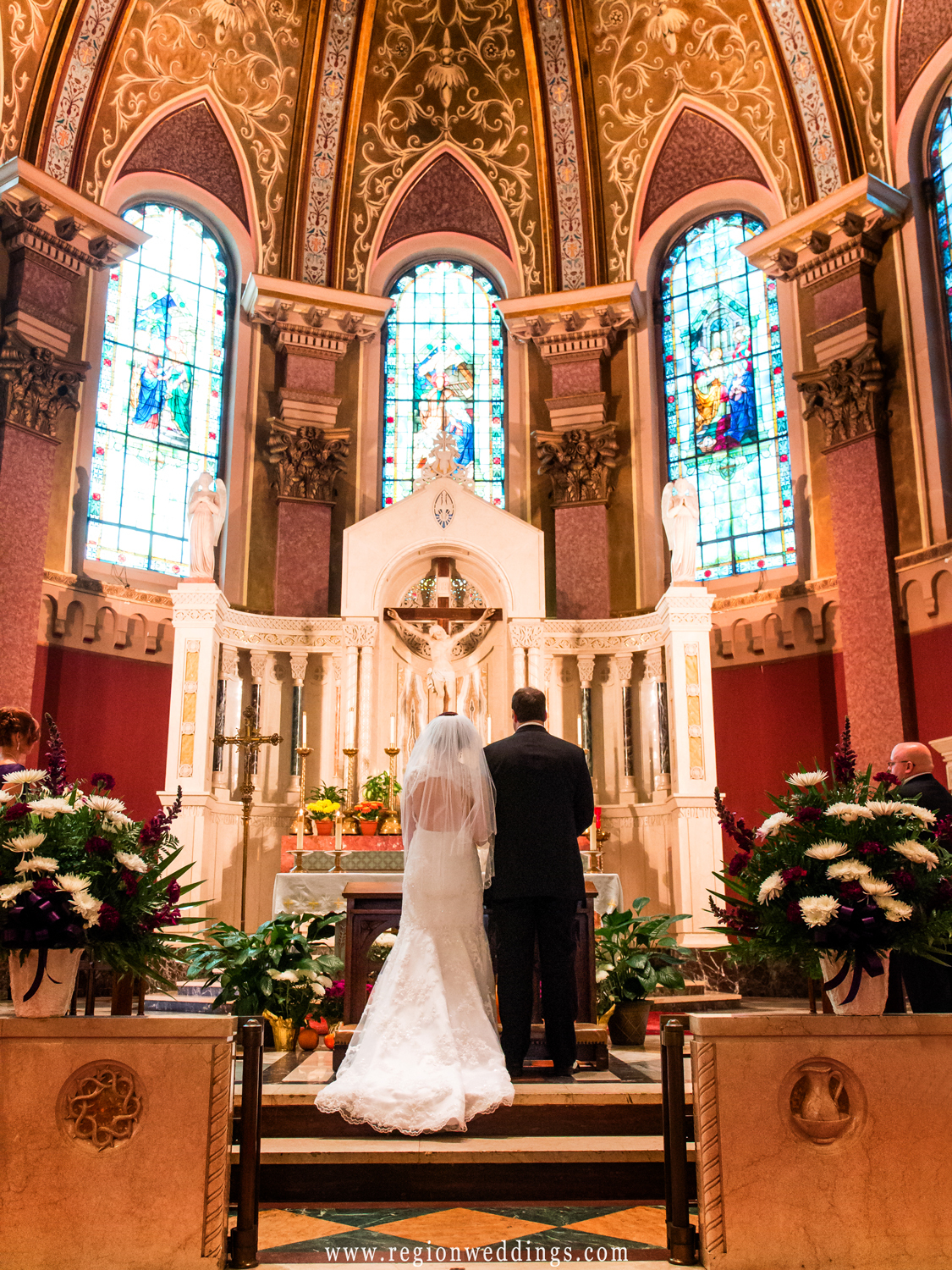 The bride and groom pray during their wedding at Saint Andrew's Church.