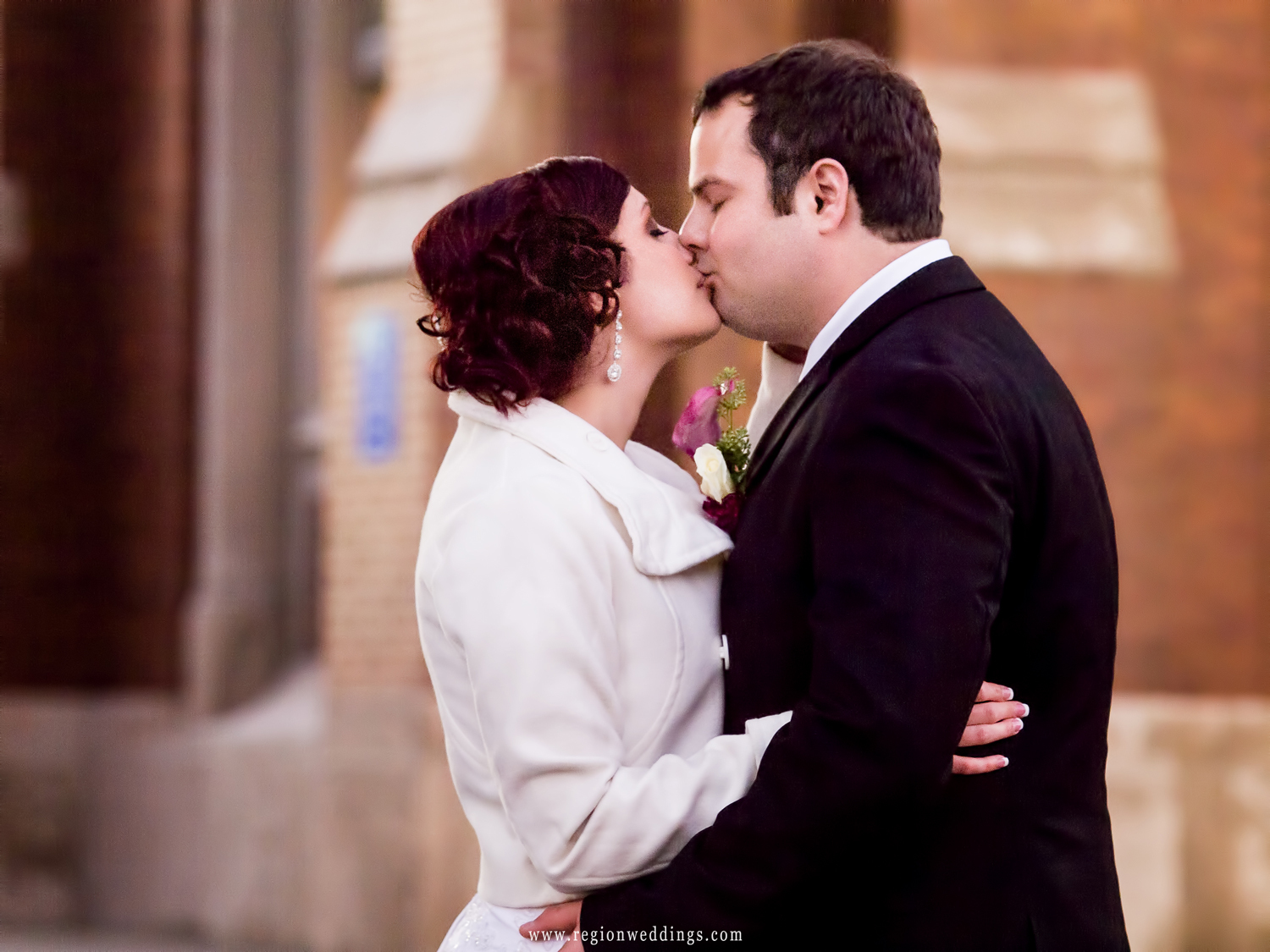 The bride and groom have a tender moment aloneoutside the steps of St. Andrew Church.