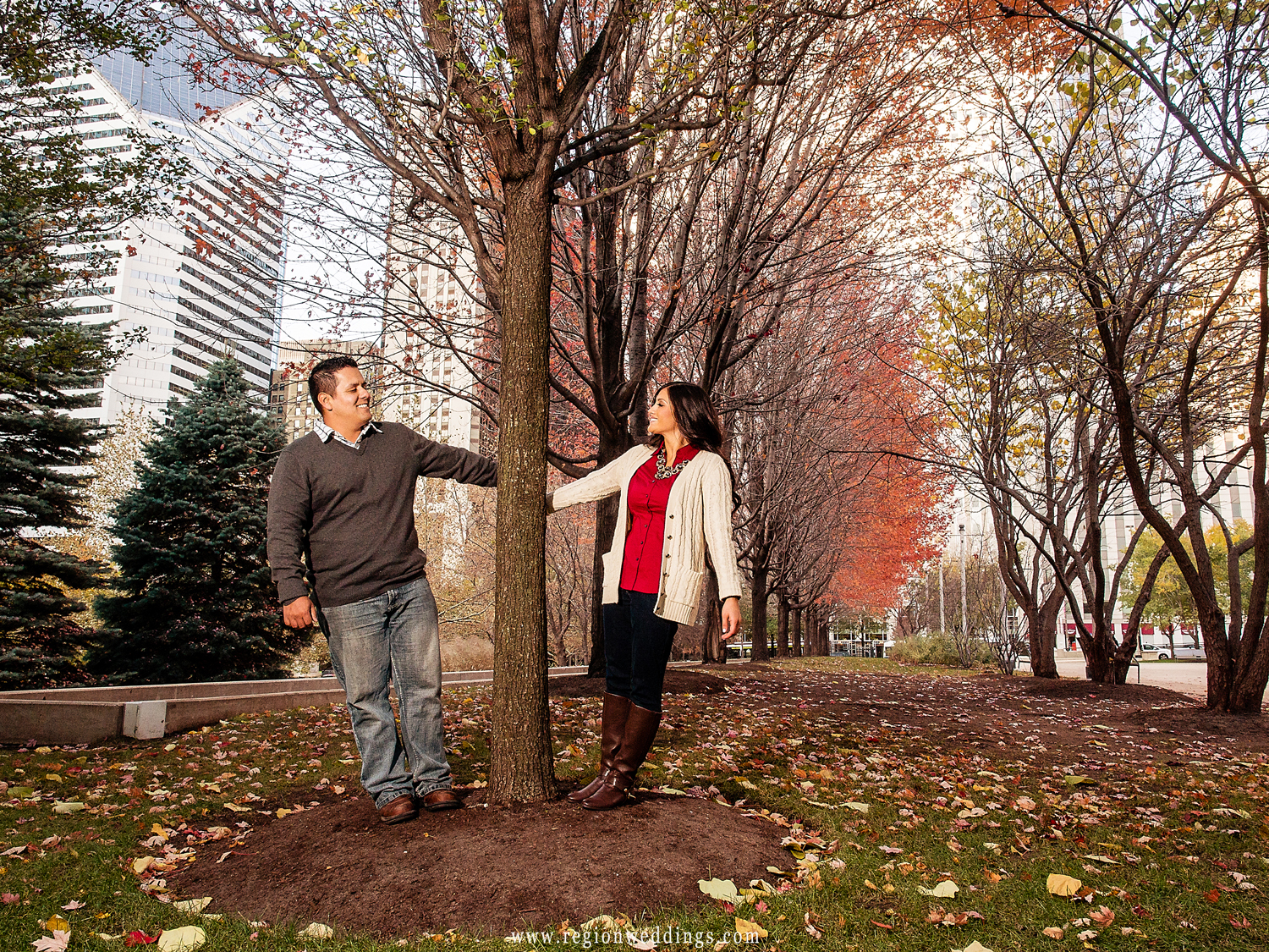 A couple playfully looks at each from each side of a large tree in Millennium Park.