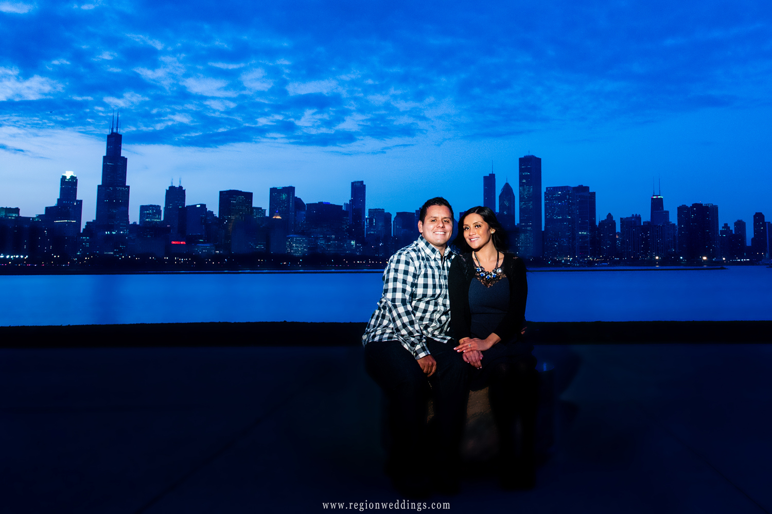 The blue Chicago skyline at dusk with a happily engaged couple sitting on the terrace of the Adler Planetarium at the Museum Campus on the lake.