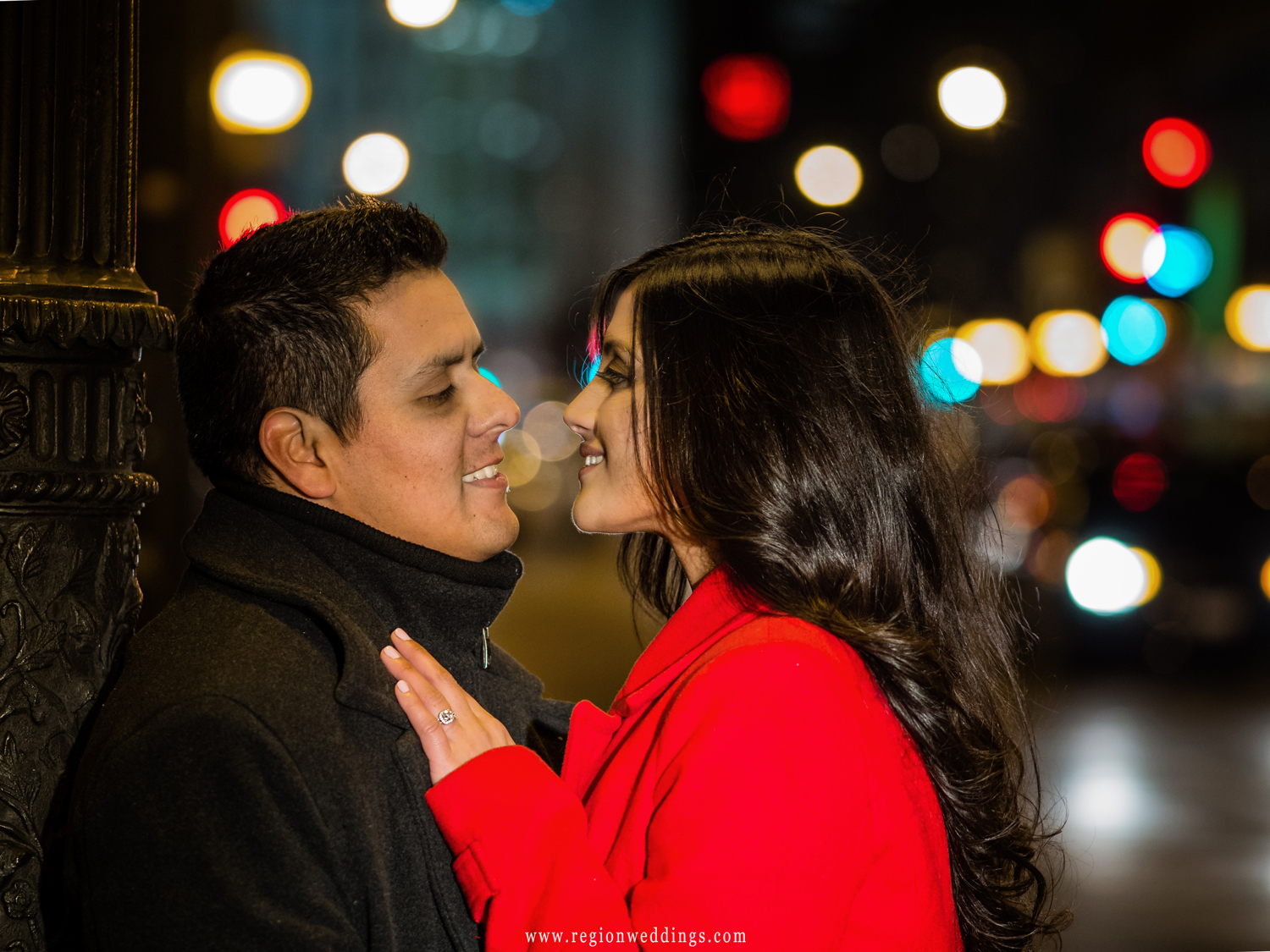 A couple tenderly embraces as city lights blur behind them at night.