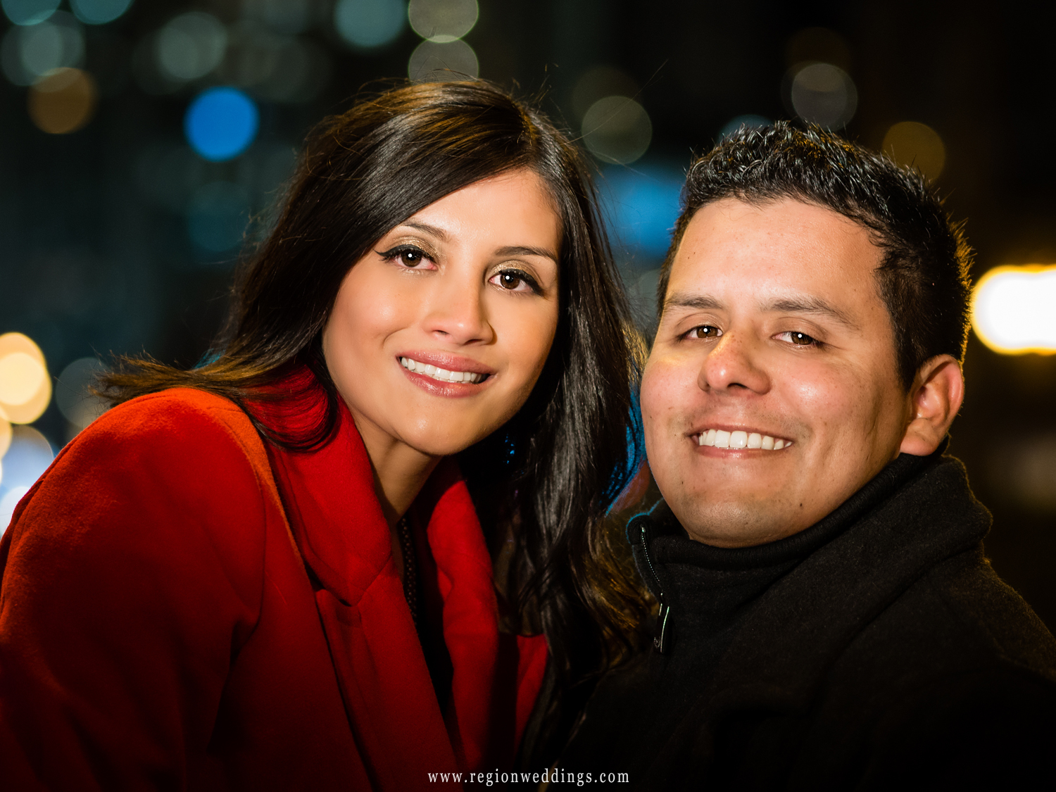 A newly engaged couple smiles for the camera on the streets of Chicago at night.