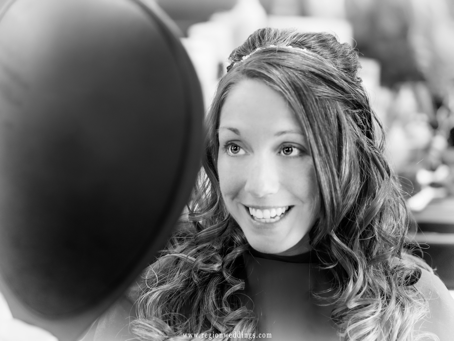 The bride smiles as she looks over her hair while getting ready for her wedding.